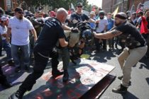 """CHARLOTTESVILLE, VA - AUGUST 12: White nationalists, neo-Nazis, the KKK and members of the """"alt-right"""" attack each other as a counter protester (R) intervenes during the melee outside Emancipation Park during the Unite the Right rally August 12, 2017 in Charlottesville, Virginia. After clashes with anti-fascist protesters and police the rally was declared an unlawful gathering and people were forced out of Lee Park, where a statue of Confederate General Robert E. Lee is slated to be removed. (Photo by Chip Somodevilla/Getty Images)"""