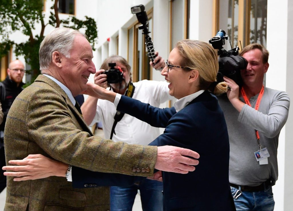 """Alexander Gauland (L) and Alice Weidel, both top candidates of Germany's nationalist Alternative for Germany (AfD) party, hug prior to a press conference in Berlin on September 25, 2017, one day after general elections. The election spelt a breakthrough for the anti-Islam Alternative for Germany (AfD), which with 12.6 percent became the third strongest party and vowed to """"go after"""" chancellor Angela Merkel over her migrant and refugee policy. / AFP PHOTO / Tobias SCHWARZ (Photo credit should read TOBIAS SCHWARZ/AFP/Getty Images)"""