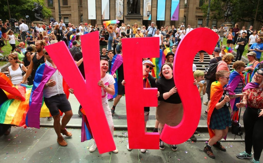 MELBOURNE, AUSTRALIA - NOVEMBER 15: People in the crowd celebrate as the result is announced during the Official Melbourne Postal Survey Result Announcement at the State Library of Victoria on November 15, 2017 in Melbourne, Australia. Australians have voted for marriage laws to be changed to allow same-sex marriage, with the Yes vote defeating No. Despite the Yes victory, the outcome of Australian Marriage Law Postal Survey is not binding, and the process to change current laws will move to the Australian Parliament in Canberra. (Photo by Scott Barbour/Getty Images)