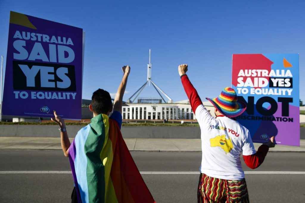 Equality ambassadors and volunteers from the Equality Campaign celebrate as they gather in front of Parliament House in Canberra on December 7, 2017, ahead of the parliamentary vote on Same Sex Marriage, which will take place later today in the House of Representatives. / AFP PHOTO / SEAN DAVEY