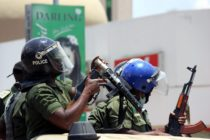 Zambian riot policeman gets ready to fire a tear gas canister to disperser Zambian traders and vendors during a march to protest over a ban on street commerce aimed at curbing a deadly cholera outbreak, in Lusaka, on January 15, 2018. Police in Zambia's capital Lusaka fired tear gas at angry traders marching to the president's office. The 500-strong crowd was trying to deliver a petition to President Edgar Lungu who has become the public face of the campaign against the outbreak that has claimed at least 70 lives since September. Authorities have banned several street markets in Lusaka in an effort to reduce the volume of food and drink sold in unsanitary open-air locations, which are particularly vulnerable to the spread of cholera. / AFP PHOTO / DAWOOD SALIM (Photo credit should read DAWOOD SALIM/AFP/Getty Images)