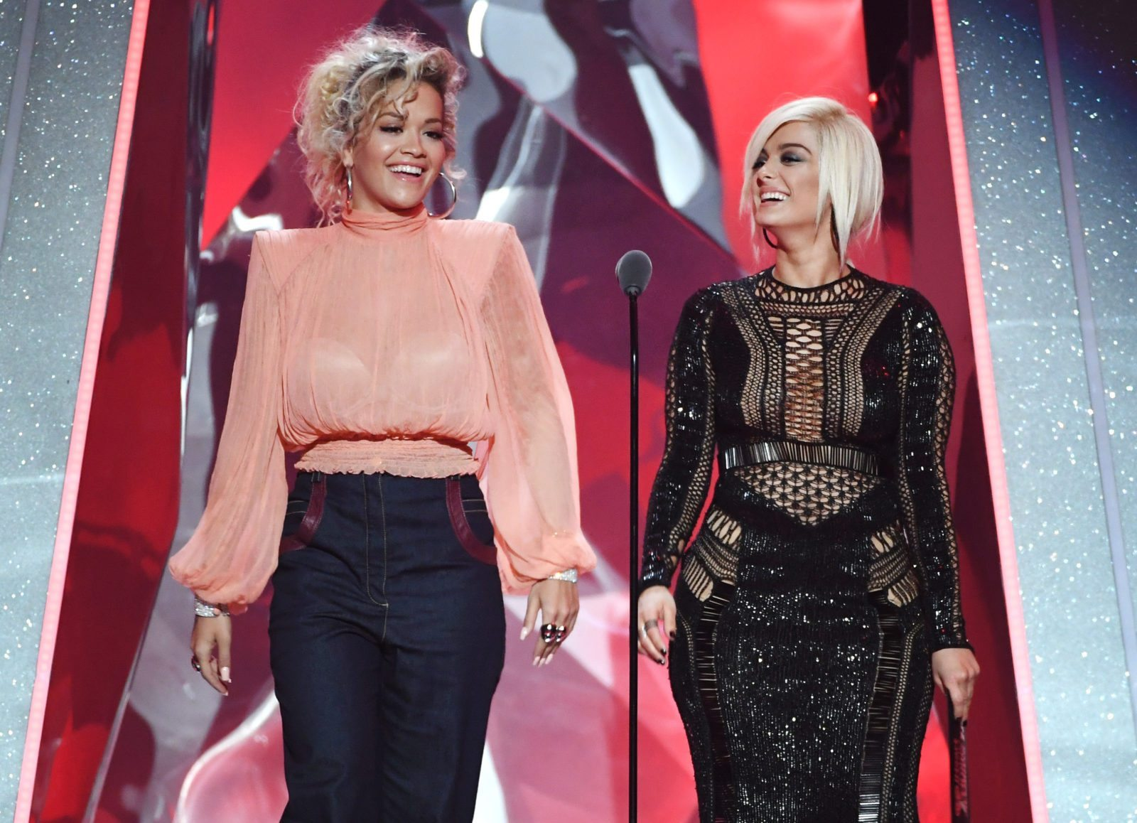 INGLEWOOD, CA - MARCH 11: Rita Ora (L) and Bebe Rexha speak onstage during the 2018 iHeartRadio Music Awards which broadcasted live on TBS, TNT, and truTV at The Forum on March 11, 2018 in Inglewood, California. (Photo by Kevin Winter/Getty Images for iHeartMedia)