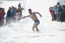 HARBIN, CHINA - MARCH 24: A man strip to the waist during the Naked Pig Skiing Carnival at the Yabuli Ski Resort on March 24, 2018 in Harbin of Heilongjiang Province, northeast China. Men stripped to the waist and women wearing swim suits attended the carnival which is held to promote skiing. (Photo by Tao Zhang/Getty Images)