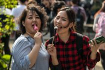 KAWASAKI, JAPAN - APRIL 01: (EDITORS NOTE: Image contains suggestive content.) Women react to the camera as they eat phallic-shaped lollipops during Kanamara Matsuri (Festival of the Steel Phallus) on April 1, 2018 in Kawasaki, Japan. The Kanamara Festival is held annually on the first Sunday of April. The penis is the central theme of the festival, focused at the local penis-venerating shrine which was once frequented by prostitutes who came to pray for business prosperity and protection against sexually transmitted diseases. Today the festival has become a popular tourist attraction and is used to raise money for HIV awareness and research. (Photo by Carl Court/Getty Images)