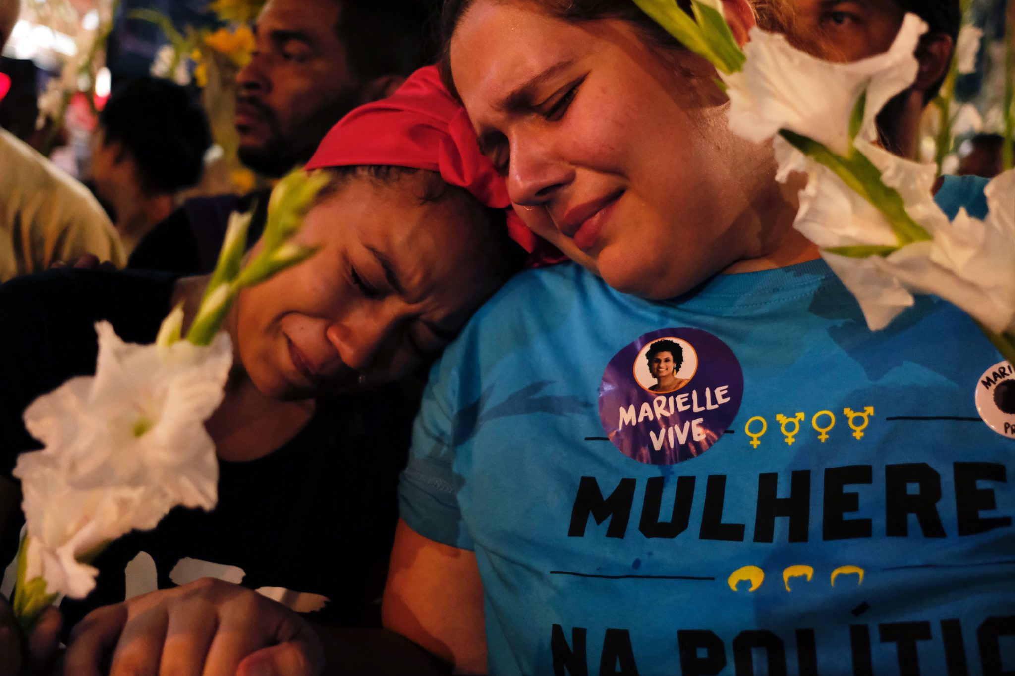 Women react at a march while mourning activist Marielle Franco in Rio de Janeiro on April 14, 2018, one month after her murder in Lapa. The murder of Franco, a black Brazilian activist who fought her way out of the slums to become a popular councilor, made headlines around the world. The outspoken 38-year-old, who was a critic of police brutality, an advocate for minorities and the posterchild of a new type of politics, was shot dead on March 14 in an assassination-style killing with four bullets to the head. / AFP PHOTO / DIEGO HERCULANO (Photo credit should read DIEGO HERCULANO/AFP/Getty Images)