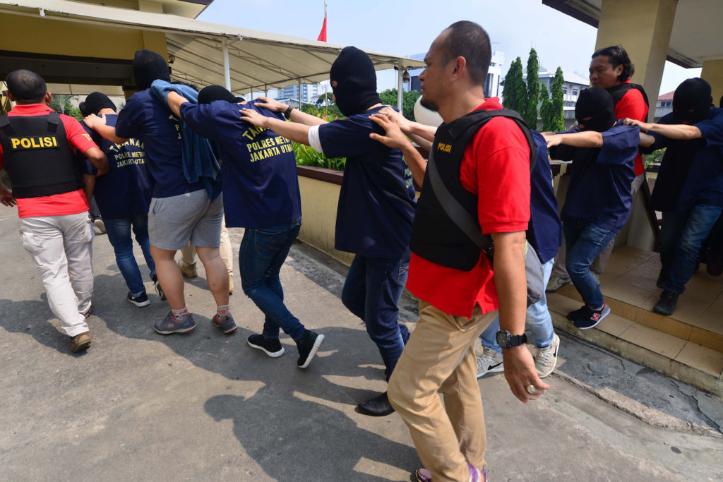 Indonesian police guard men arrested in a recent raid during a press conference at a police station in Jakarta on May 22, 2017. Indonesian police have detained 141 men who were allegedly holding a gay party at a sauna, an official said on May 22, the latest sign of a backlash against homosexuals in the Muslim-majority country. / AFP PHOTO / FERNANDO (Photo credit should read FERNANDO/AFP/Getty Images)