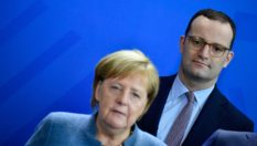 German Health Minister Jens Spahn stands behind Chancellor Angela Merkel