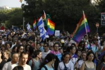 Participants wave Israeli and LGBT pride rainbow flags during Jerusalem's annual Gay Pride parade on August 2, 2018.