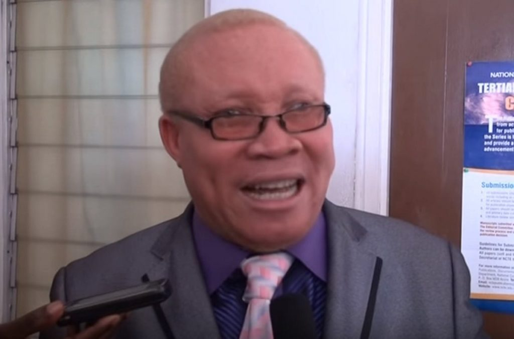 Moses Foh-Amoaning in a purple shirt and grey blazer talking to the camera