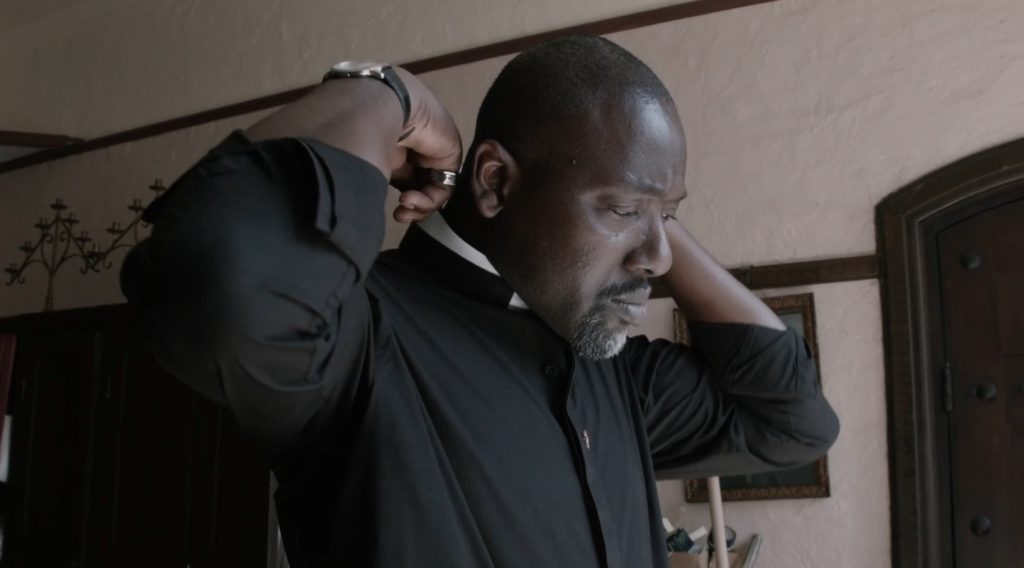 Openly gay priest Reverend Jide Macaulay wears the clerical collar during a clip of Stonewall's BAME Voices documentary.