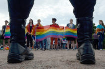 People wave rainbow flags during a pride rally in Saint Petersburg, on Agust 12, 2017 as police look on.