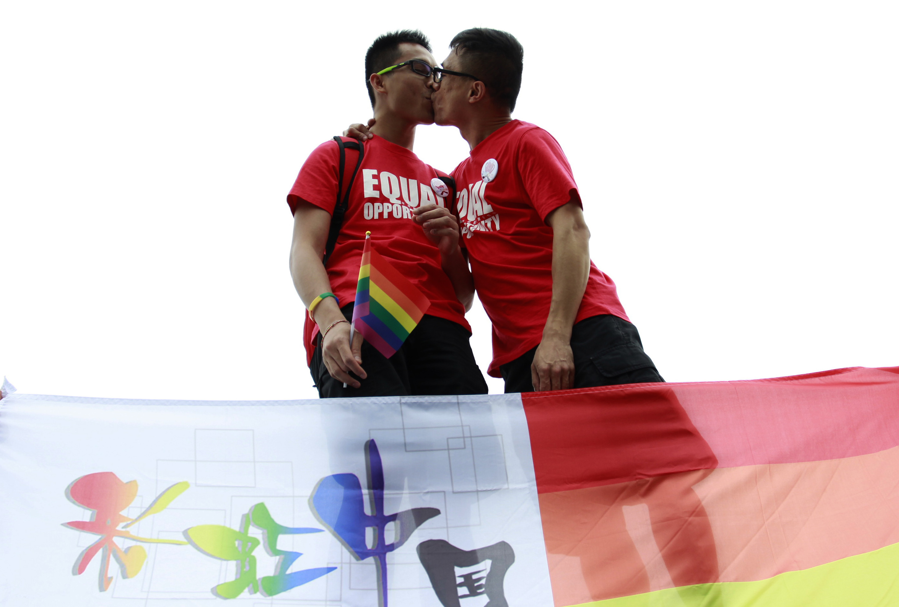 A gay couple kiss at an anti-discrimination parade in Chine, where a writer was recently jailed for including gay sex scenes in her novel.