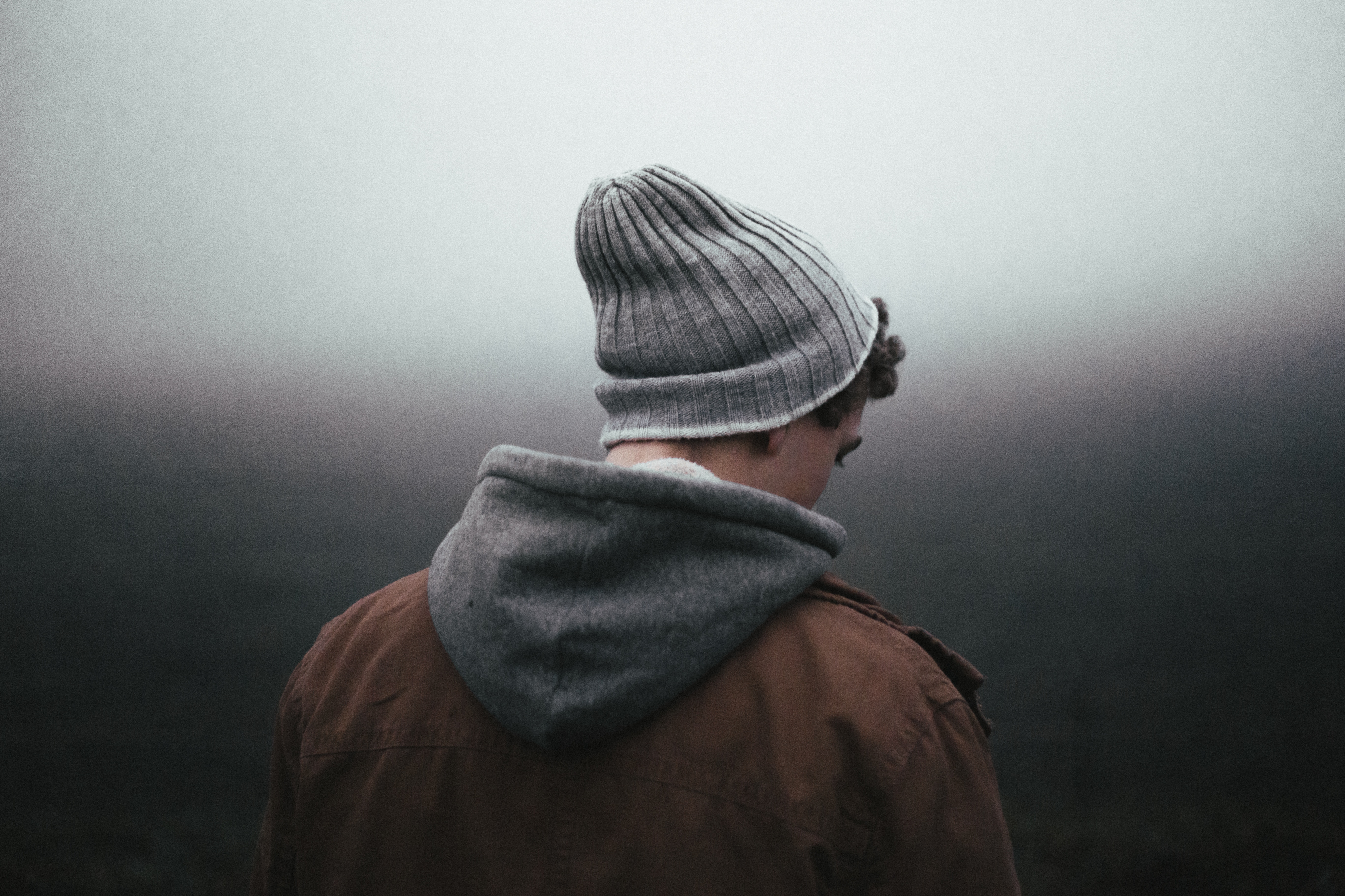 A man wearing a beanie hat and hoody looking away from the camera
