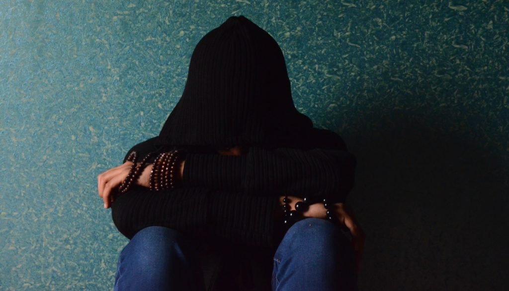 A teenager sits with their face covered by a black hoodie