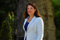 Caroline Nokes wearing a white jacket walking into 10 Downing Street