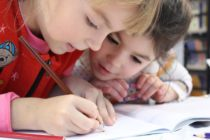 Two children draw a picture together, similar to the images Russian Police seized from a school.