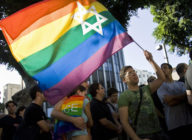 An Israeli man waves a Pride rainbow flag bearing the Star of David
