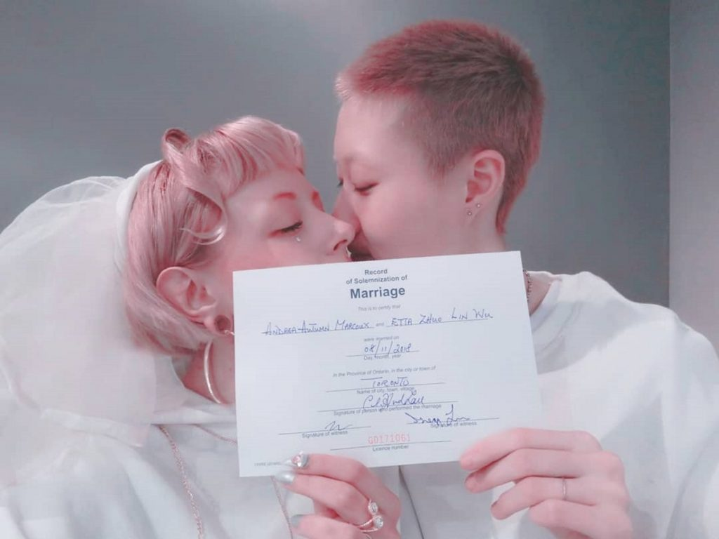 Jackie Chan's daughter Etta Ng and Andi Autumn pose with their wedding certificate