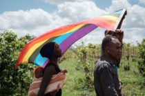 Two LGBT+ refugees and a child march holding a rainbow flag