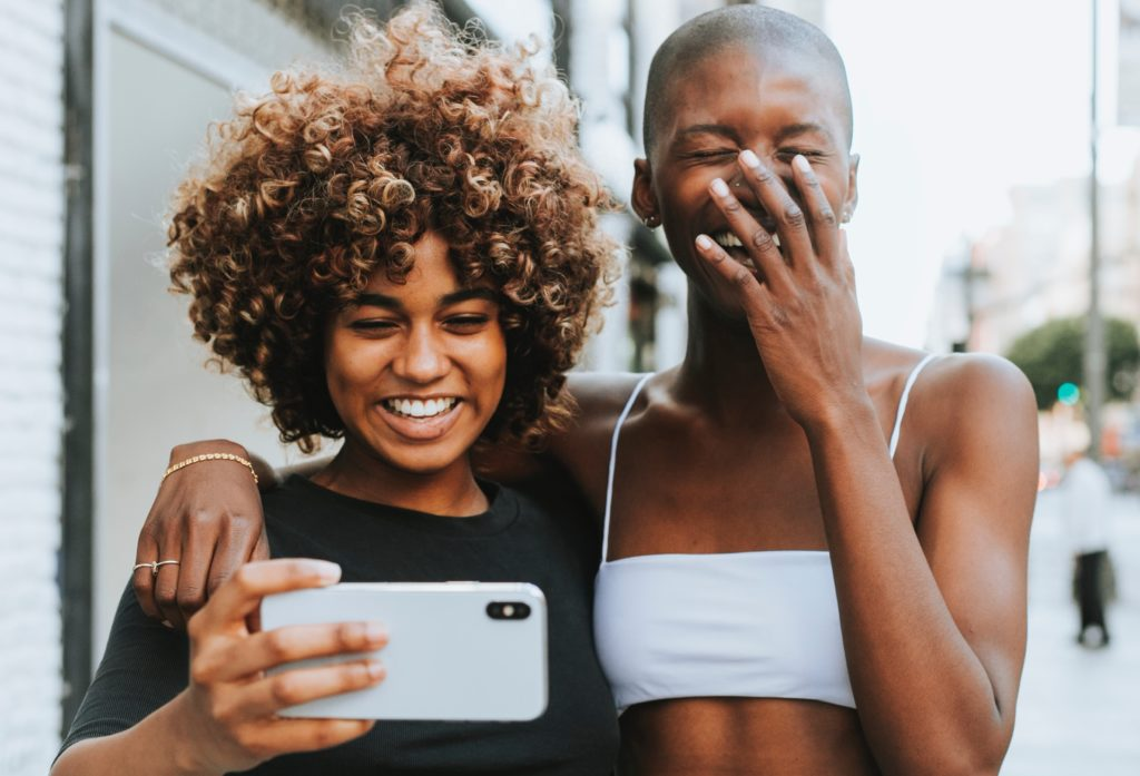 Two women smile while taking a photo of themselves