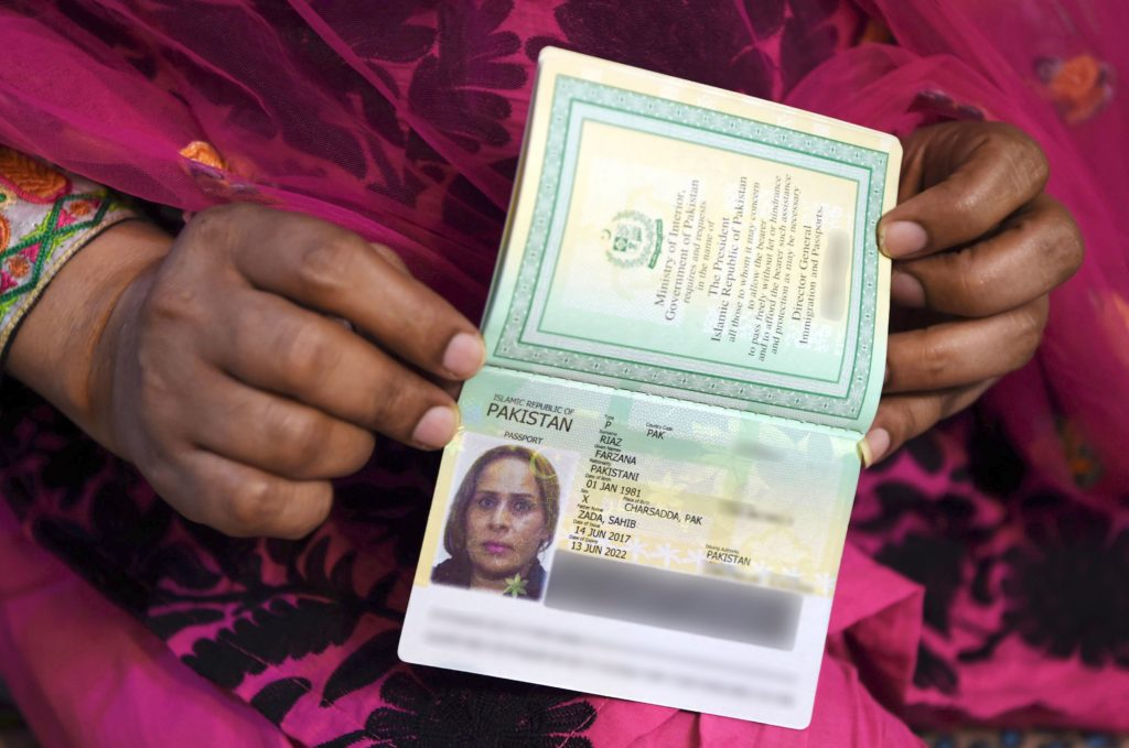 A close up of hands holding a non-binary passport.
