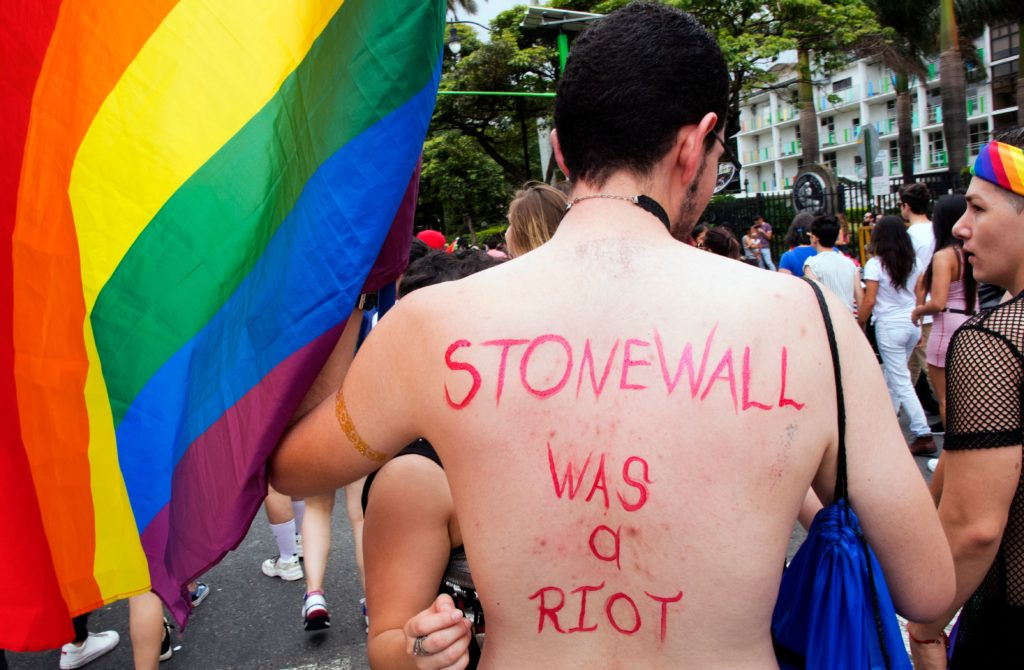 A topless man with 'Stonewall was a riot' written on his back