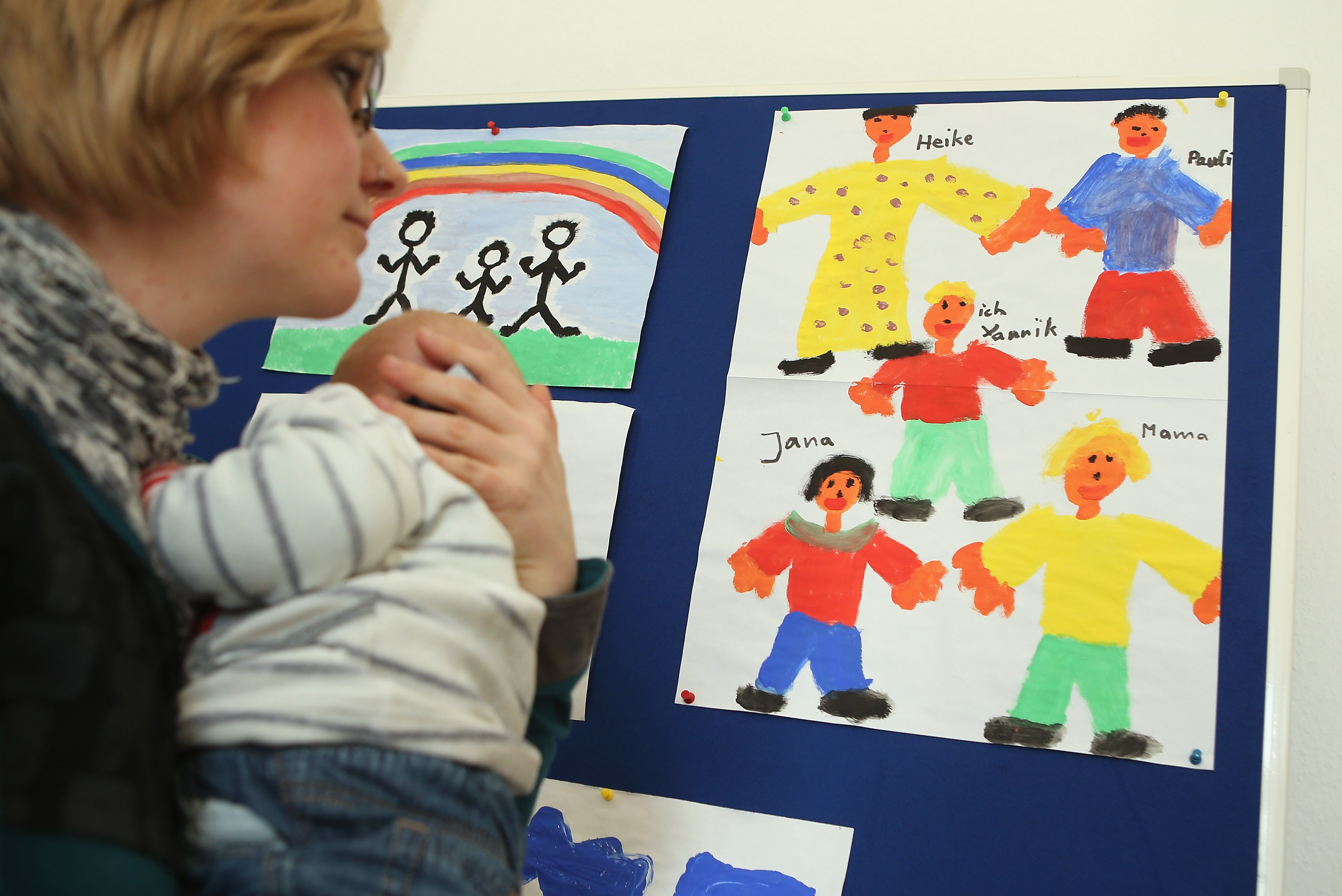 A woman holding a baby looking at drawings. She is at Germany's first gay parent counselling centre.