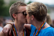 Gay stories: gay kiss with people where rainbow pride lanyards