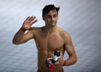Tom Daley shirtless and waving