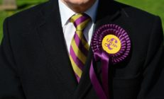 A voter wears a UK Independence Party (UKIP) rosette as he stands outside a polling station in Brighton, southern England on May 7, 2015, as Britain holds a general election. Polls opened Thursday in Britain's closest general election for decades with voters set to decide between the Conservatives of Prime Minister David Cameron, Ed Miliband's Labour and a host of smaller parties. AFP PHOTO / GLYN KIRK (Photo credit should read GLYN KIRK/AFP/Getty Images)