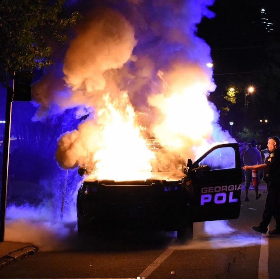 A police car on fire at the protest