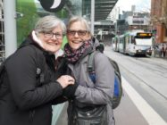 Women holding hands at tram stop