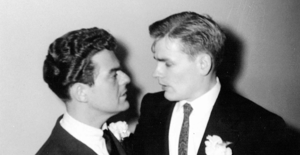 Two grooms looking at each other lovingly