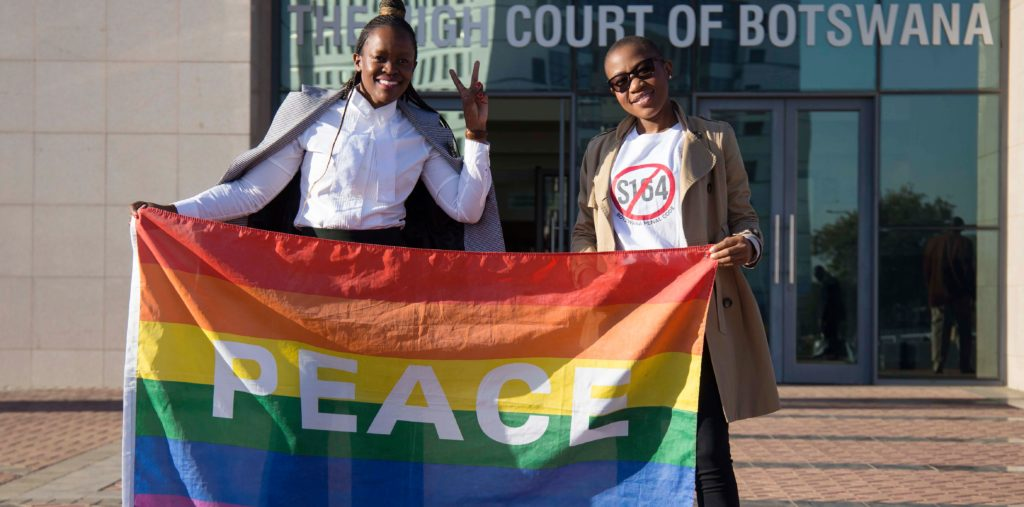 Activists pose with a rainbow flag as they celebrate outside Botswana High Court in Gaborone on June 11, 2019.
