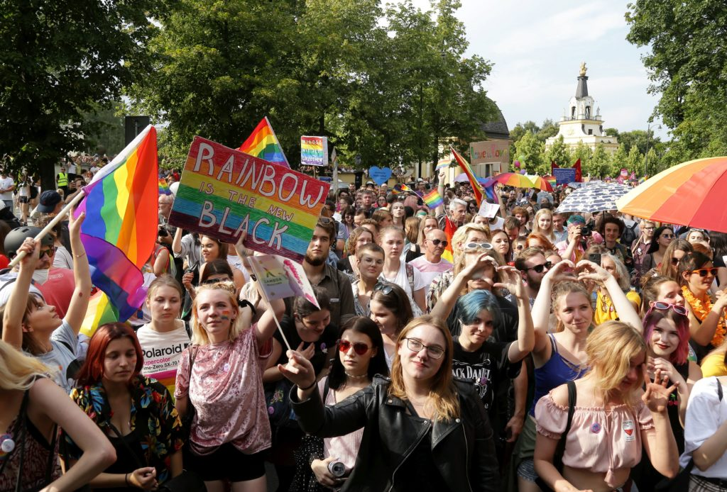 People hold flags and placards during the first gay pride march on July 20, 2019 in Bialystok