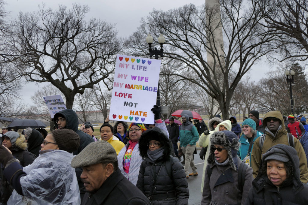 A woman holds a pro-LGBT placard on a Martin Luther King Day march. File photo.