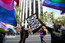 Men wave rainbow and 'black lives matter' flags while marching in the annual LGBTQI Pride Parade on Sunday, June 25, 2017 in San Francisco, California.
