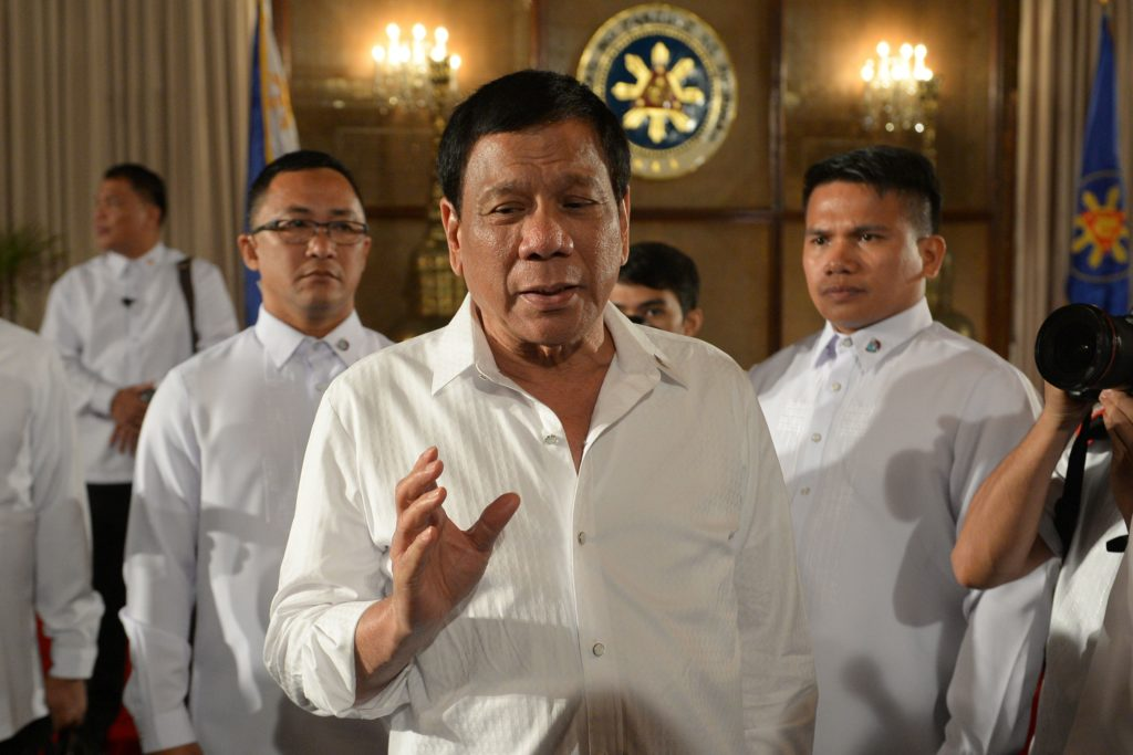 Rodrido Duterte flanked by two other men