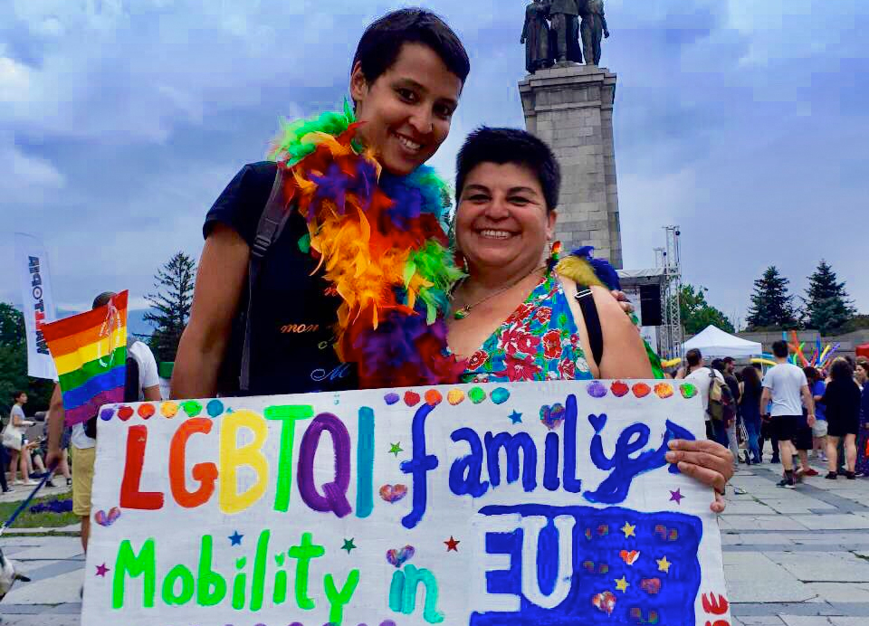 "Crstina Palma and her wife holding a sign reading ""LGBTQI family mobility in EU"""