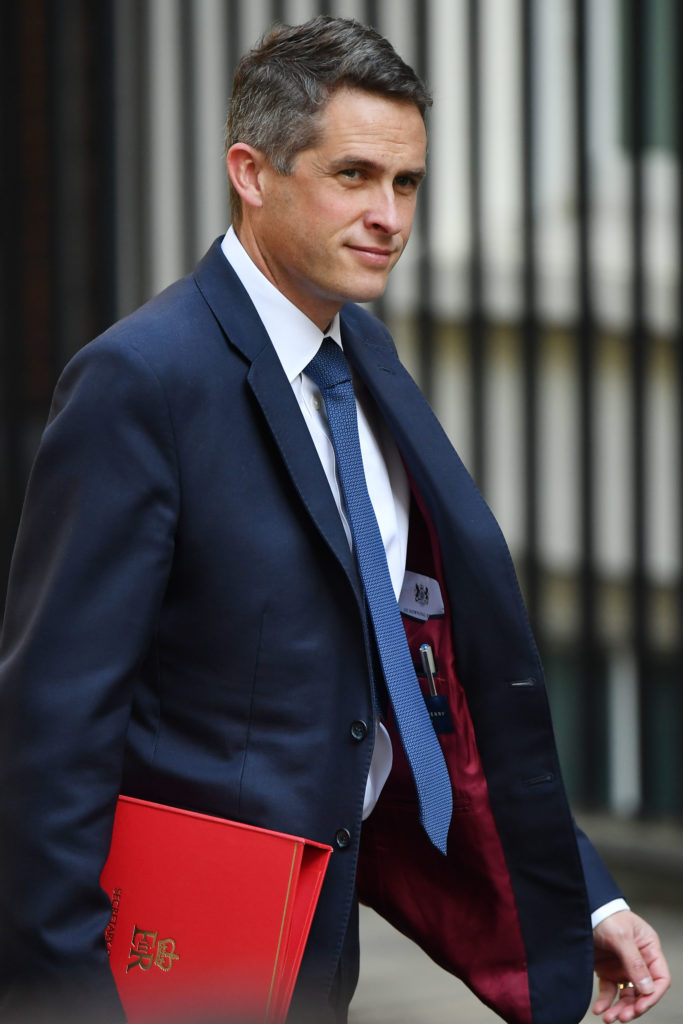 Gavin Williamson holding a red portfolio