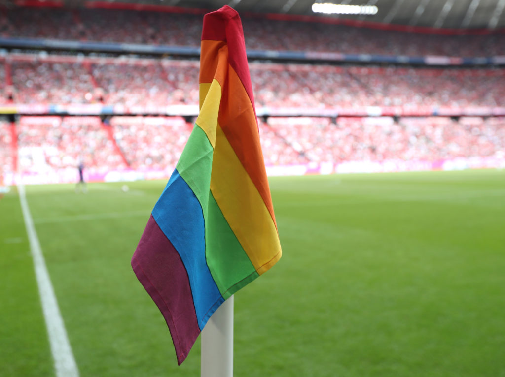 A rainbow corner flag flying on a football pitch
