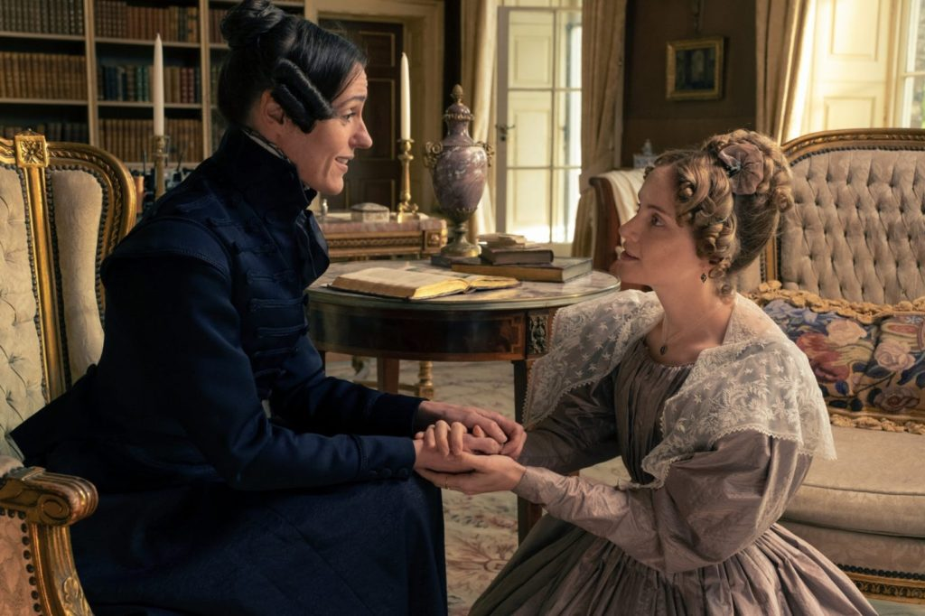 Anne Lister sitting down, holding hands with Ann Walker who is on bended knee