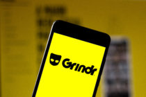 A phone showing a yellow screen with the Grindr logo