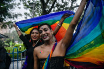 Two smiling people hold a rainbow flag