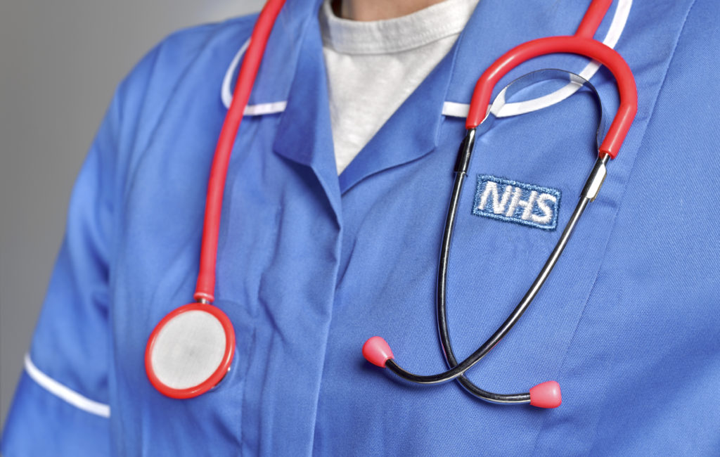A close-up of somebody wearing an NHS uniform with a stethoscope around their neck.