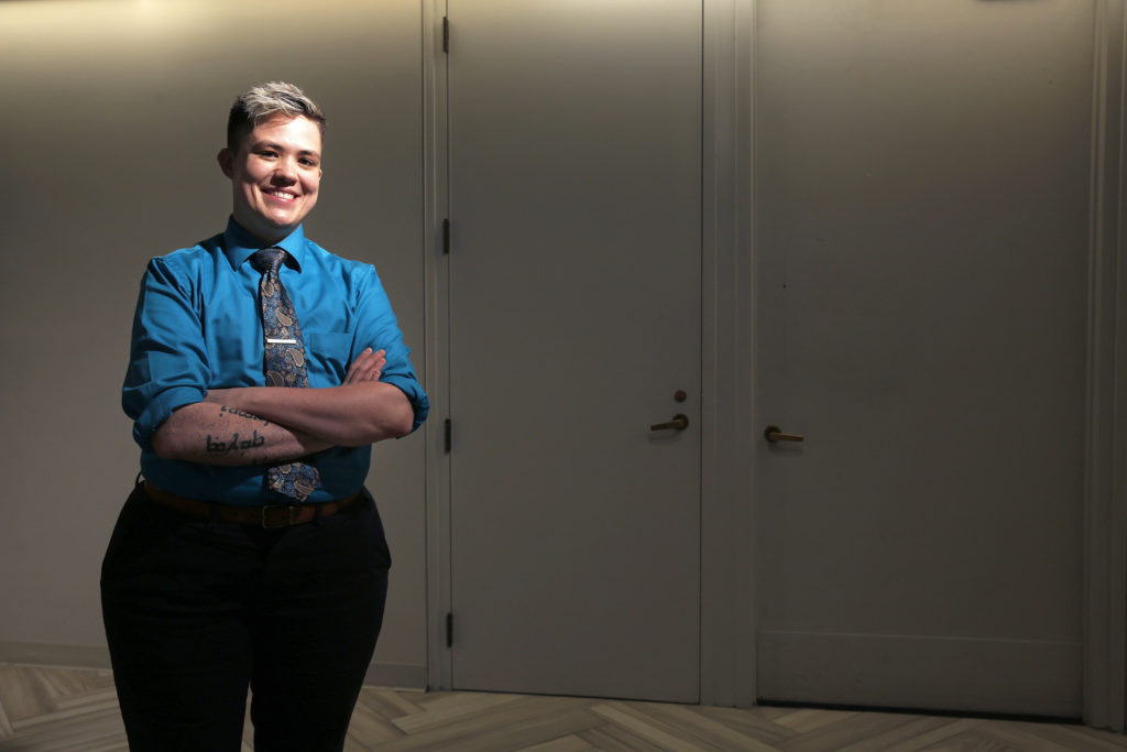 Ian-Meredythe Dehne Lindsey, a non-binary person, smiling and crossing their arms.