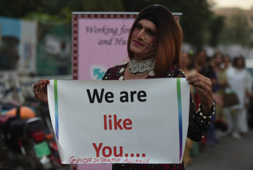 """A Pakistani transgender activist holding a sign saying """"we are like you."""""""
