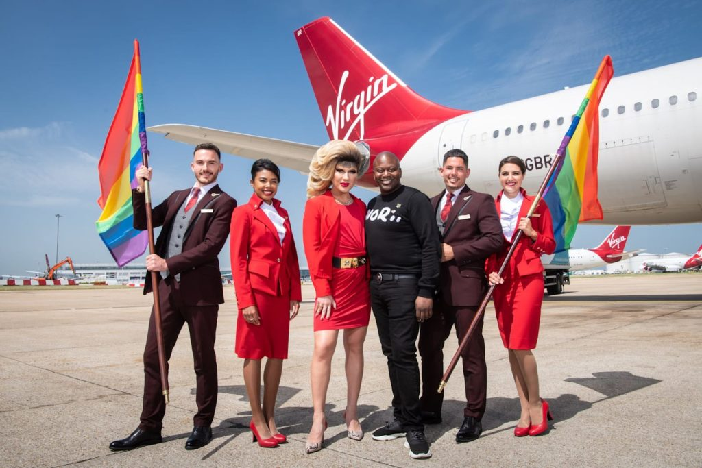 LGBT+ flight crew hold rainbow flags alongside Jodie Harsh and Tituss Burgess