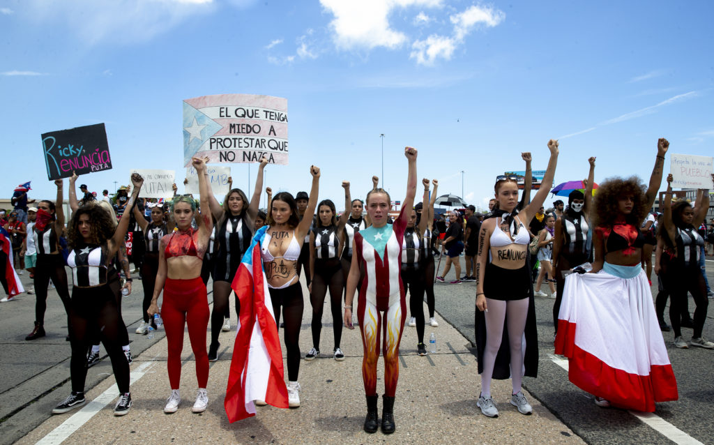 Women protestors stand in the middle of a highway