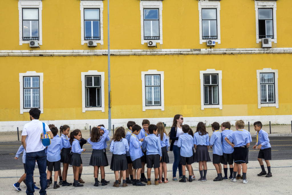 A row of school children in shorts and skirts